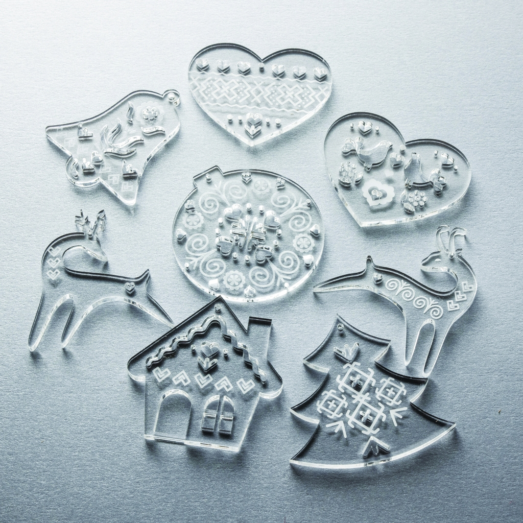 A set of laser cut and engraved transparent acrylic Christmas ornaments with Cicmany pattern.